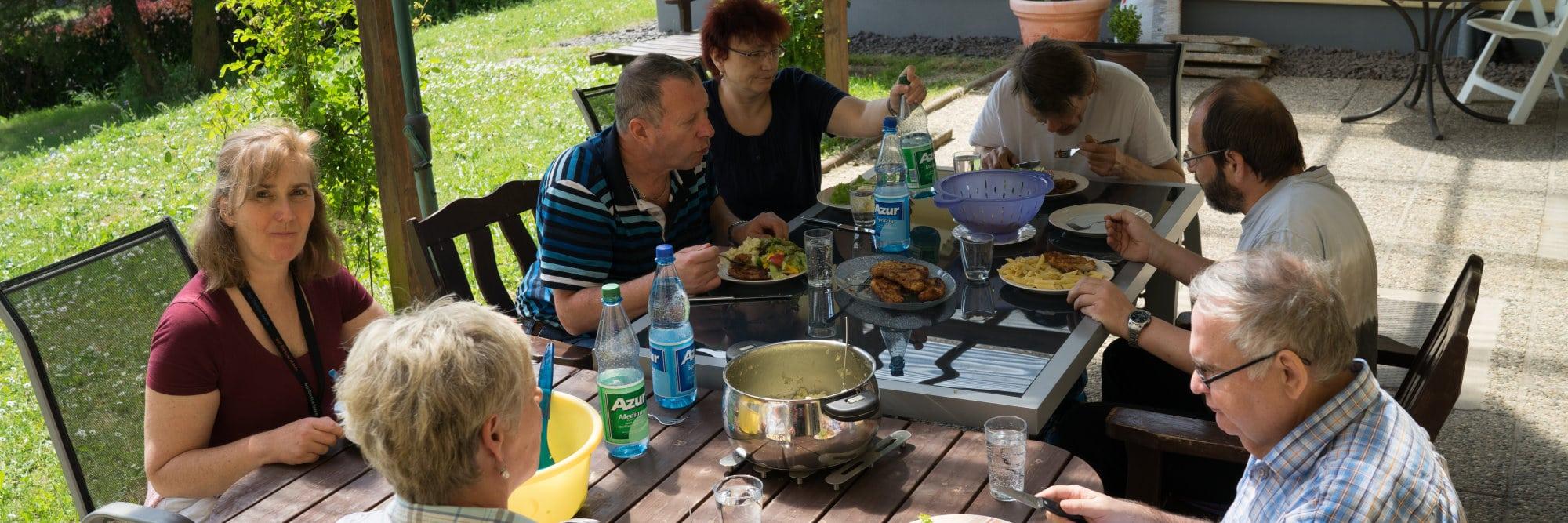 Eine Gruppe von Menschen sitzt auf der Terrasse an einem Tisch und nimmt gemeinsam eine Mahlzeit ein.